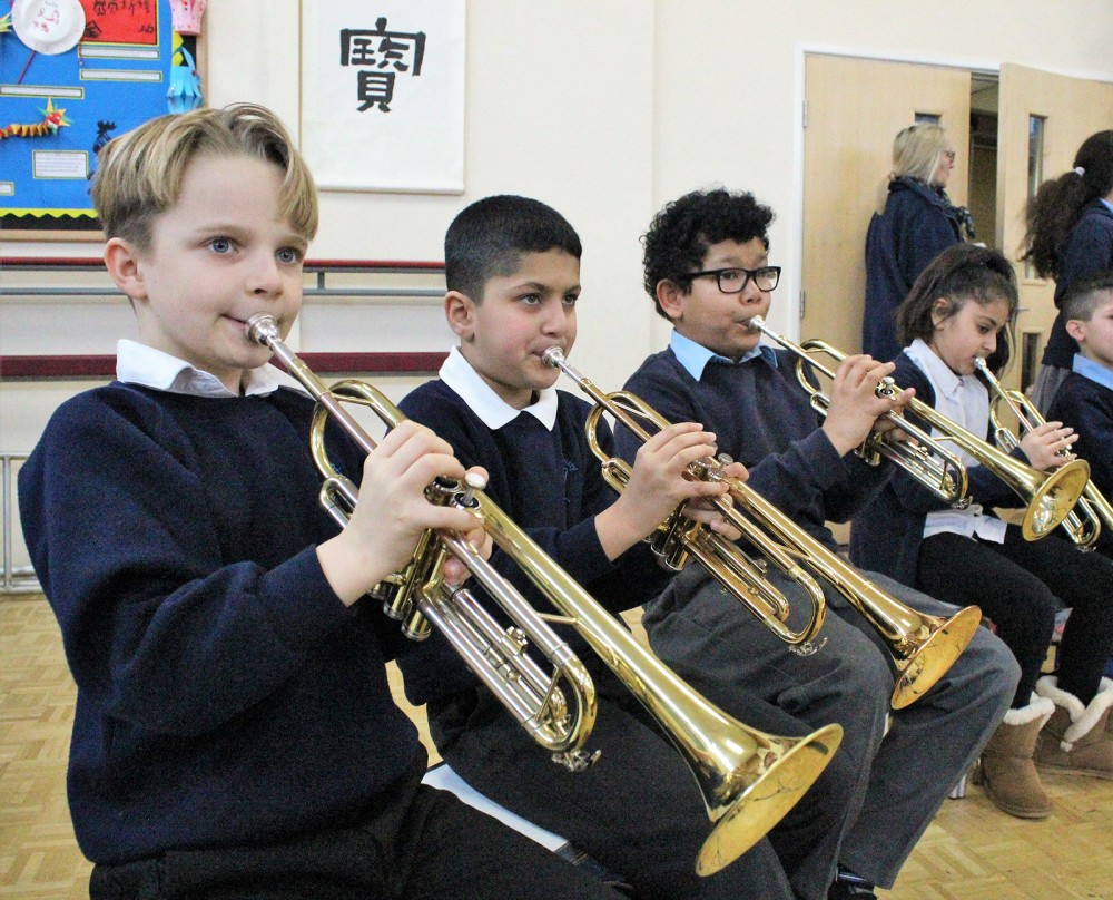 Pupils at a primary school in the city playing trumpets during their Whole Class Ensemble lesson